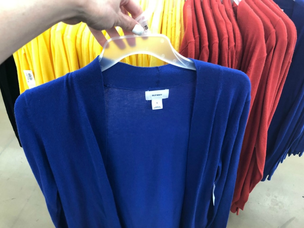 Hand holding women's open-front sweater on hanger near in-store display