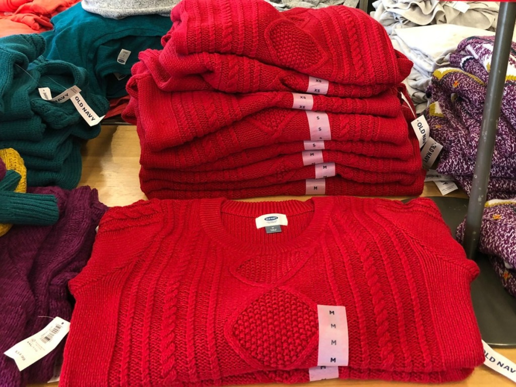 Red women's sweaters in a stack on display in a store