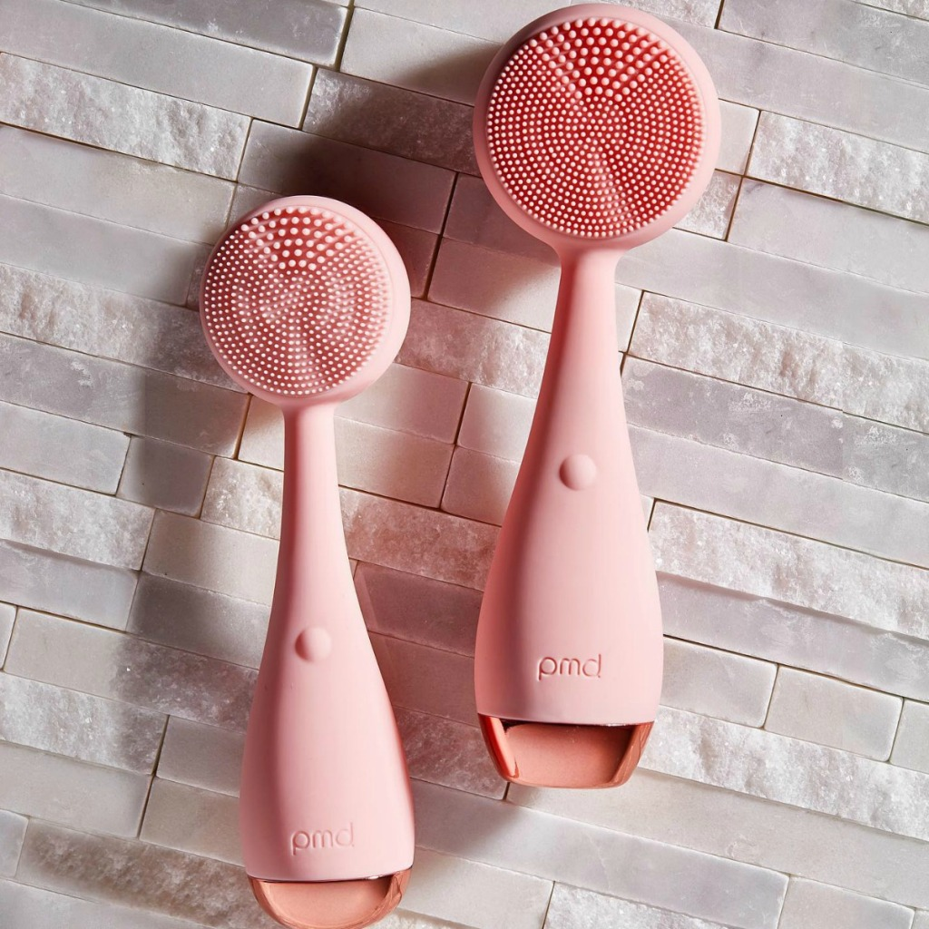 Two blush pink colored facial cleaning tools