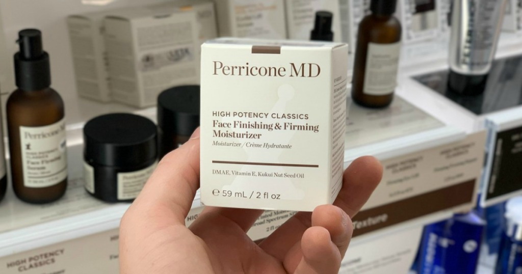 Box of moisturizer in hand near in-store display