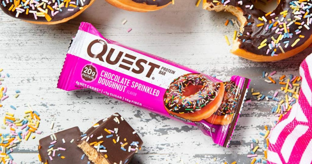 Quest Chocolate Sprinkled Doughnut Protein Bar with multiple chocolate doughnuts displayed