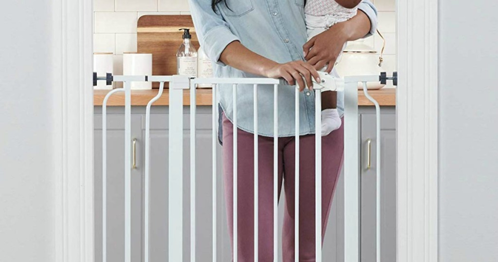 woman holding a baby walking through a gate