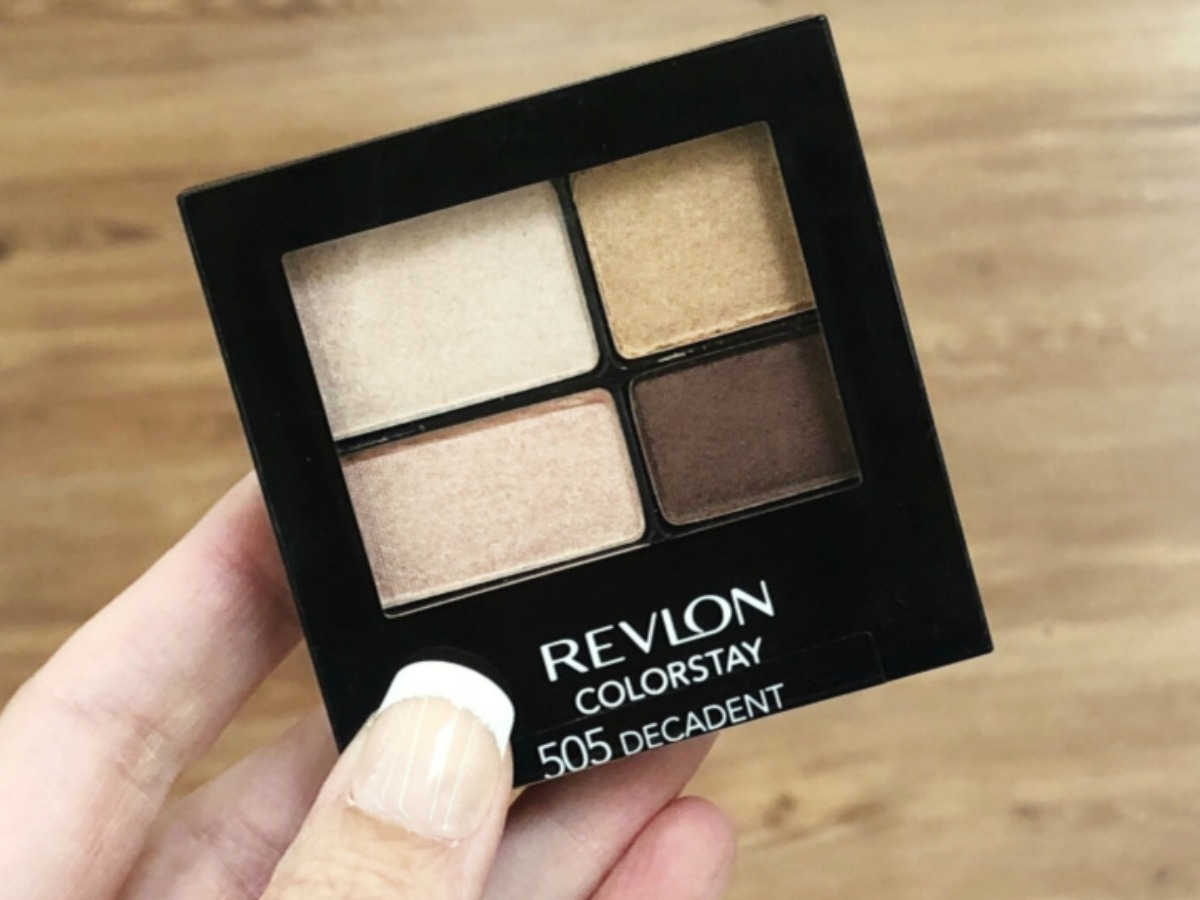 Hand holding a small eye shadow palette with four shades of brown and cream