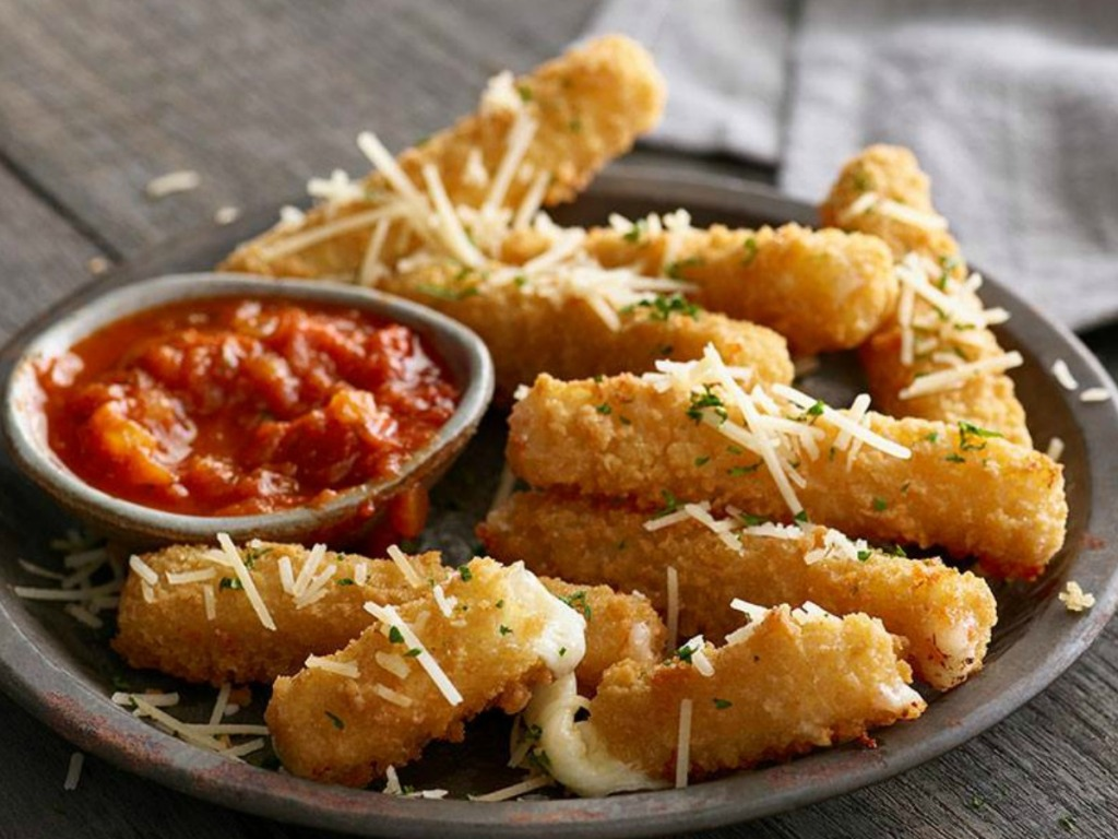 Large plate full of fried mozzarella sticks with a dipping container of marinara sauce
