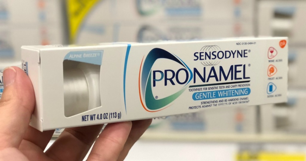 Sensodyne brand toothpaste in hand in-store in front of display