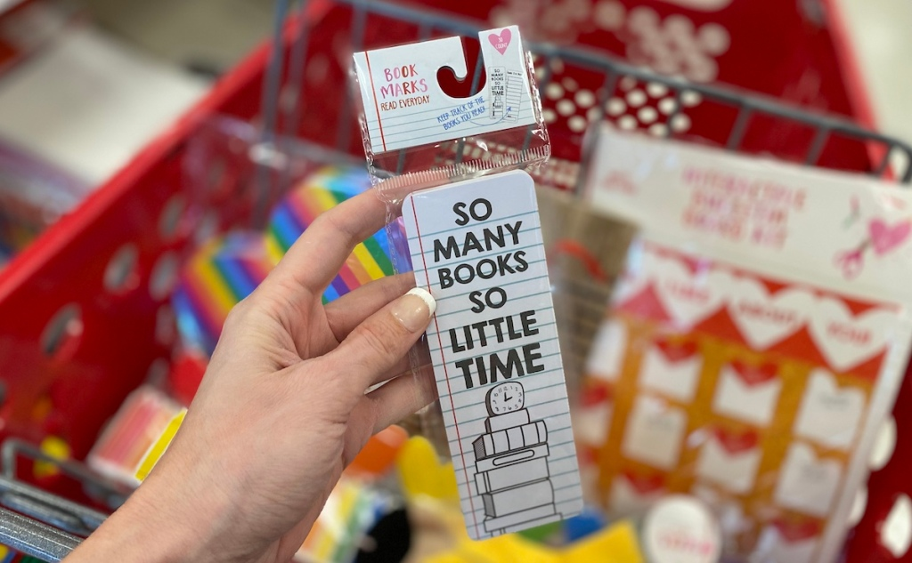 hand holding pack of So Many Books Book Markers in front of Target cart