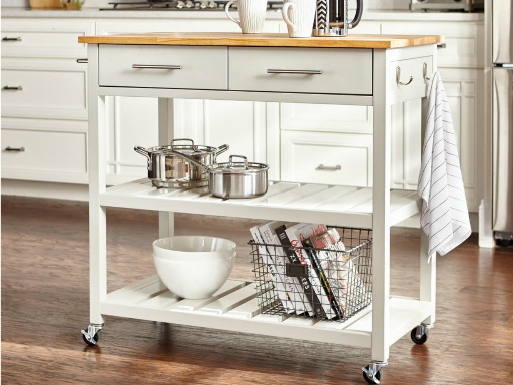 White kitchen cart with wheels and drawers and wood counter in kitchen