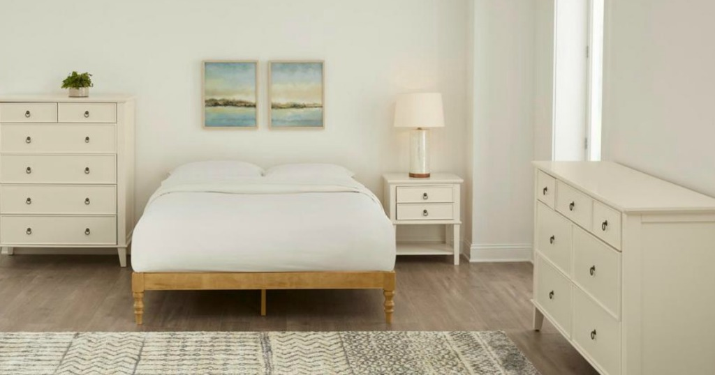 platform bed in bedroom with dressers and nightstand