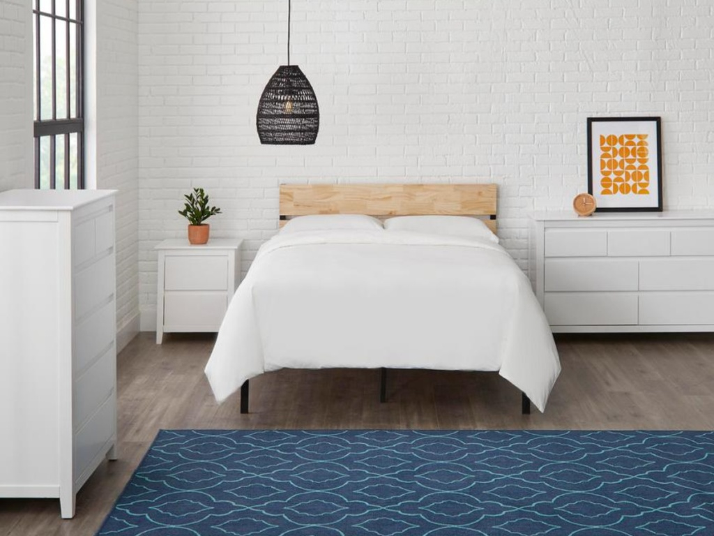 wood platform bed with white blanket and white furniture