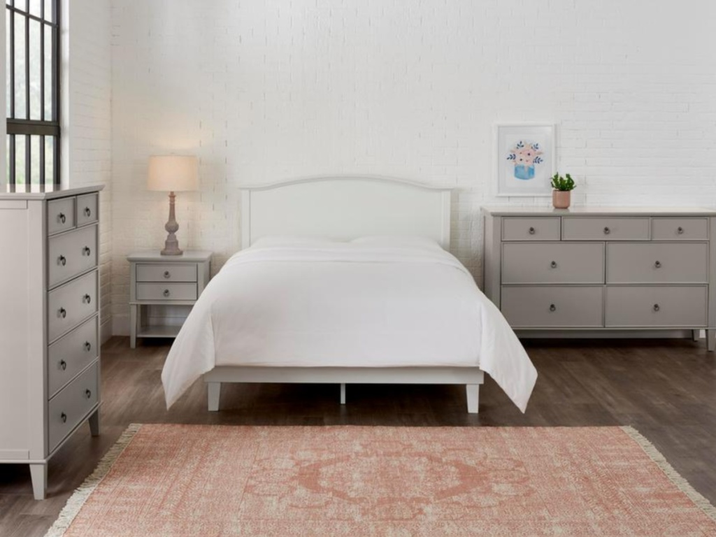 white platform bed in bedroom with grey furniture