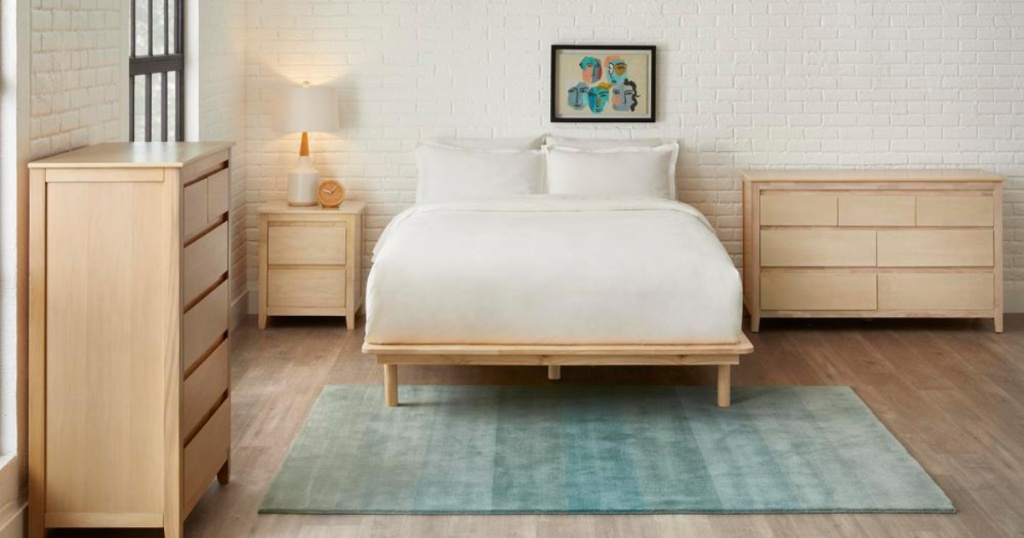 light wood platform bed with white blanket and wood furniture