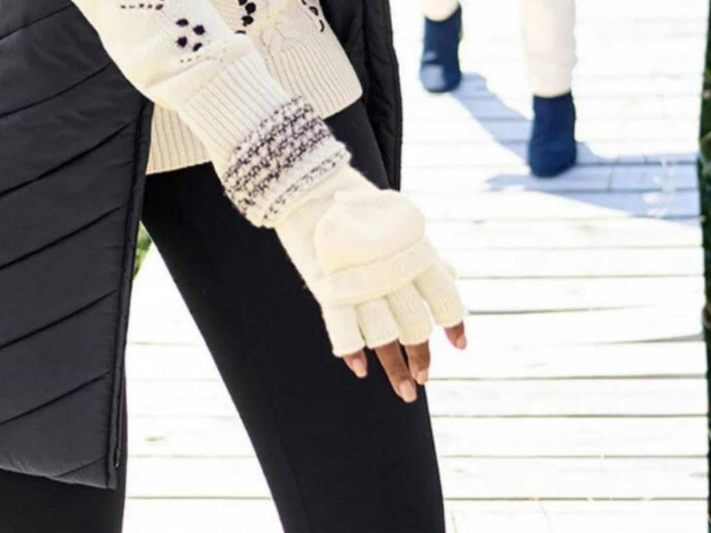 Woman wearing ivory gloves on boardwalk
