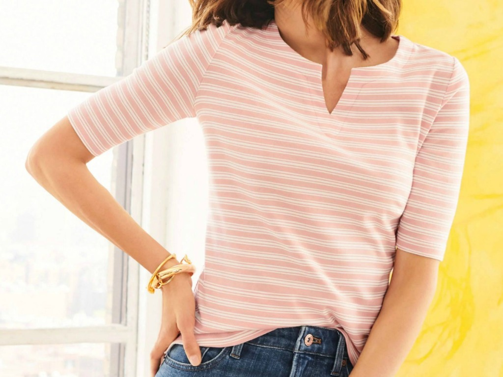 Woman wearing a coral colored strip tee with jeans