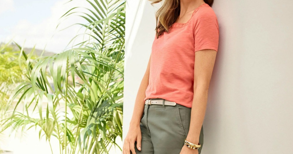 Woman wearing a coral colored shirt with green pants standing outside