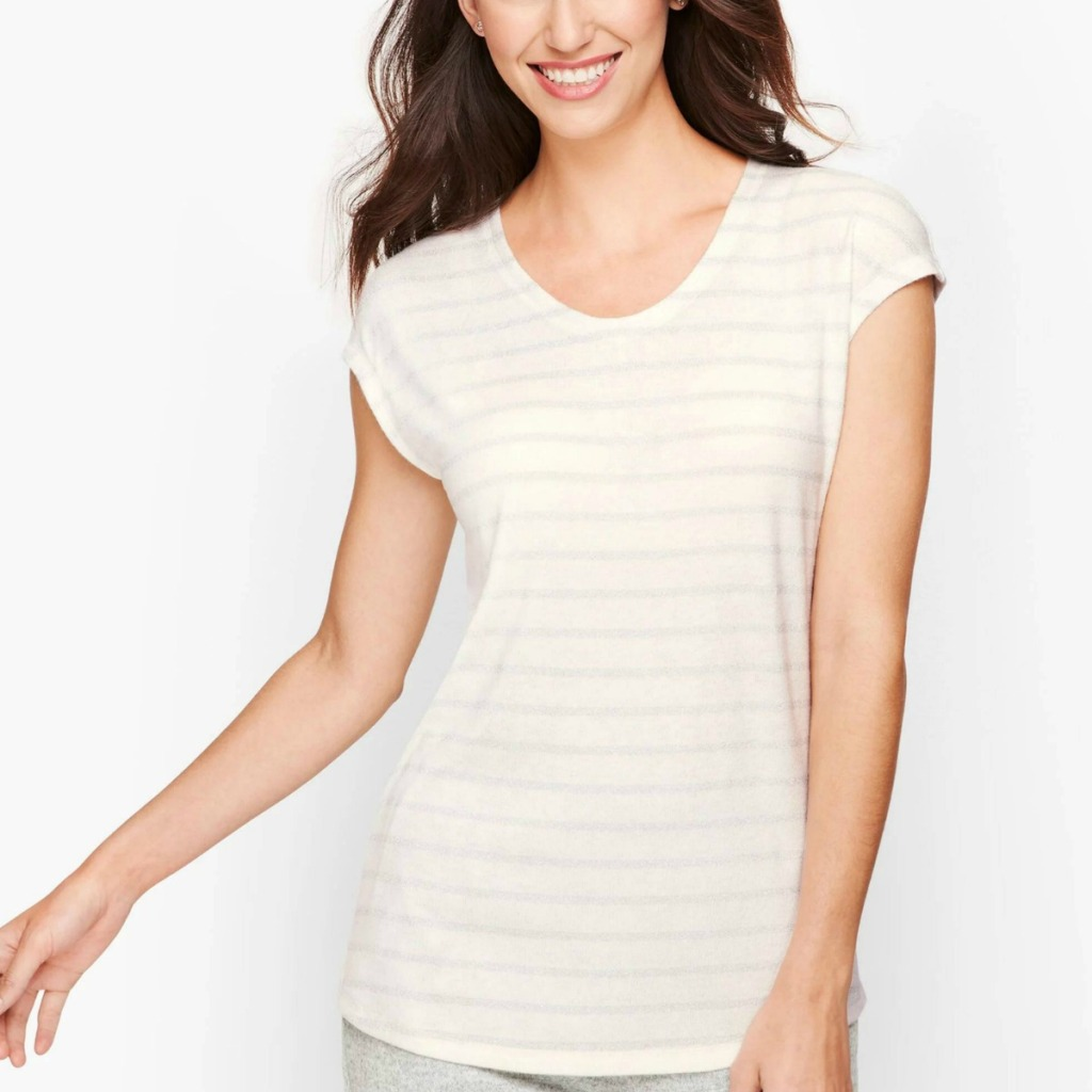 Woman wearing a long ivory tee with shimmering stripes