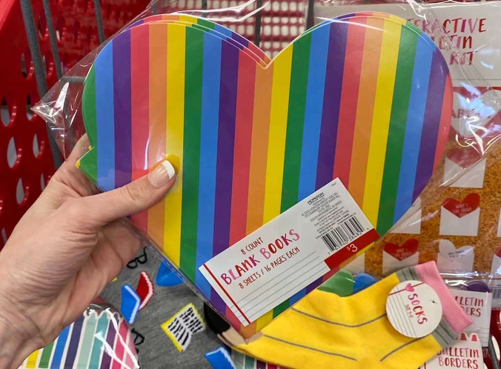 hand holding pack of heart shaped blank books in front of Target cart