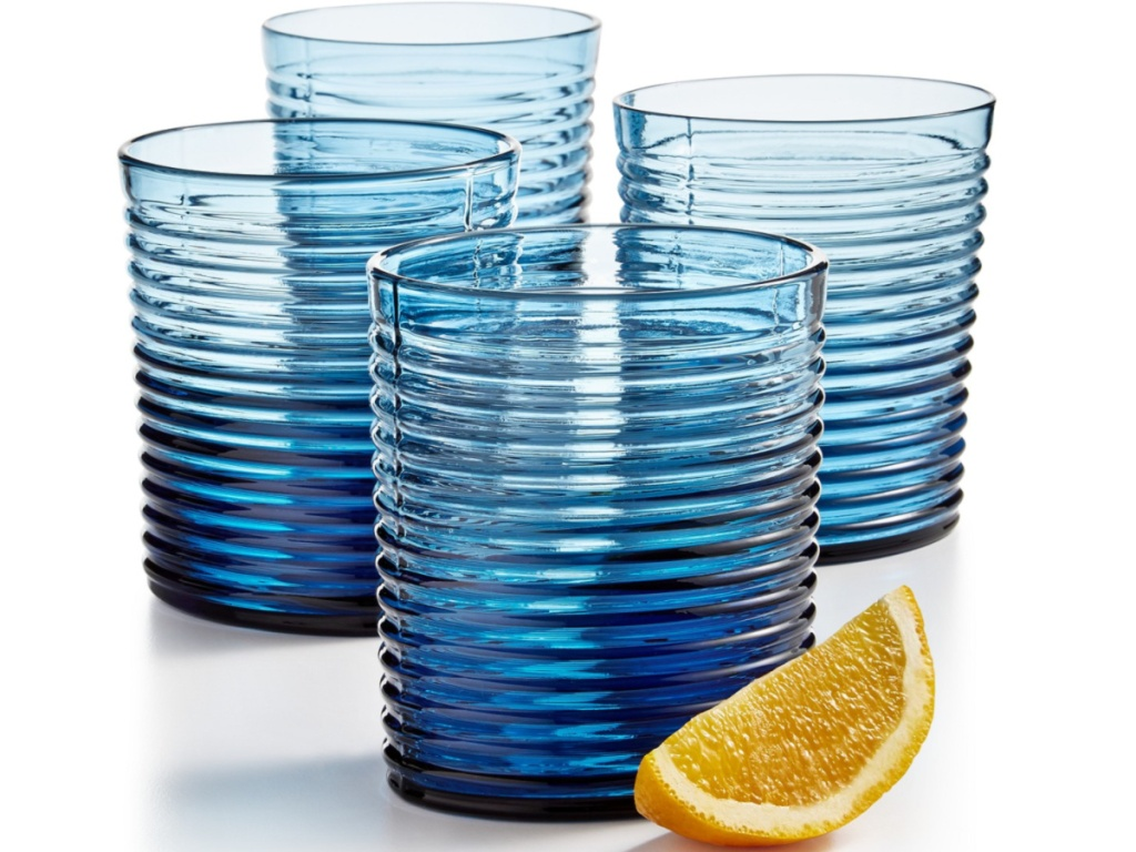 four short blue glasses with a lemon wedge beside them