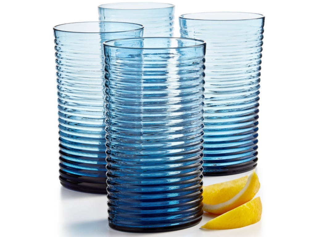 four blue tall glasses with a lemon beside the glasses