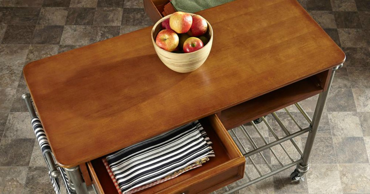 An extra large wooden kitchen cart with bowl of apples on top