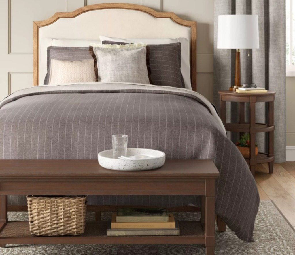 brown wooden bench at the end of a bed