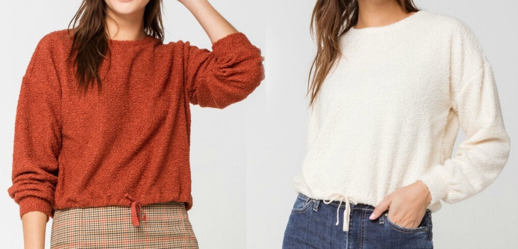 Two women wearing two different colors of cinch-tie sweaters