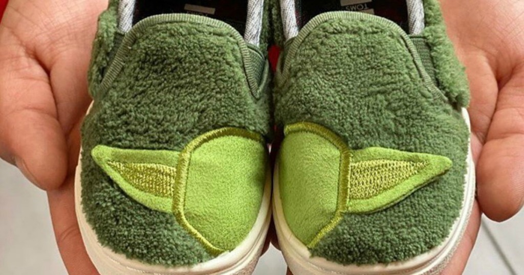 Tiny TOMS Yoda shoes in a pair of hands