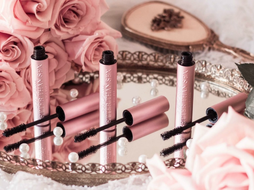 Three tubes of pearly pink mascara on a mirror near matching pink roses