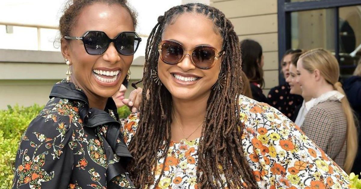 Two Women smiling side by side wearing Sunglasses