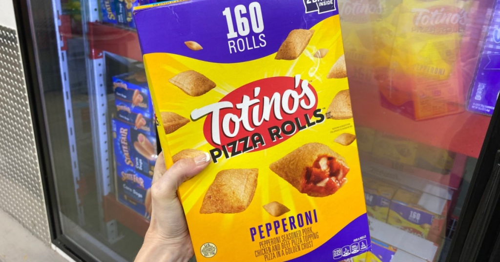 hand holding Tostino's pizza rolls in front of refrigerator in store