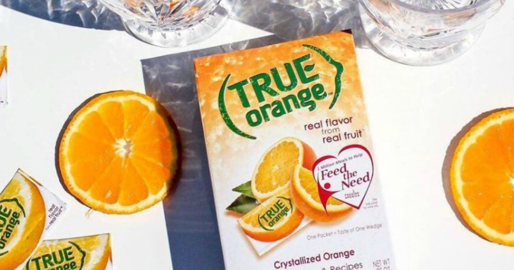 box of True Orange surrounded by iced glasses and sliced oranges