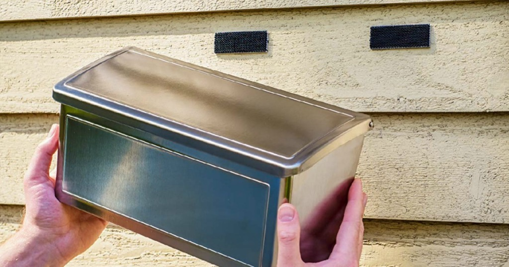 Velcro strips fastening a mailbox onto a house