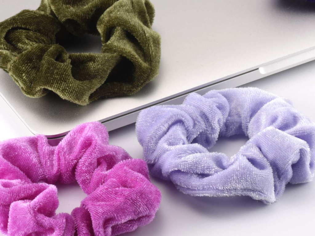 Three velvet scrunchies sitting on a laptop