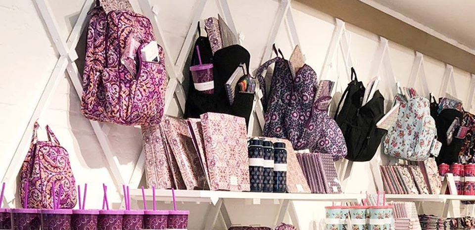 Vera Bradley Backpacks hanging on wall by journals and notebooks