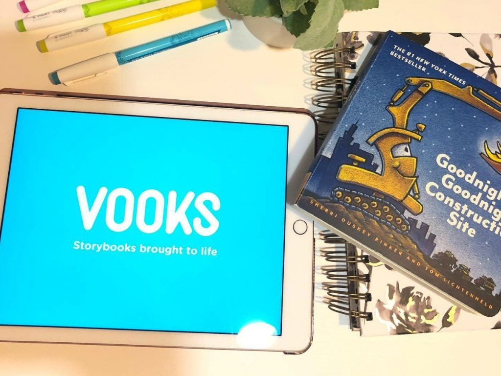 Vooks app open on a tablet near a story book and writing utensils on table top
