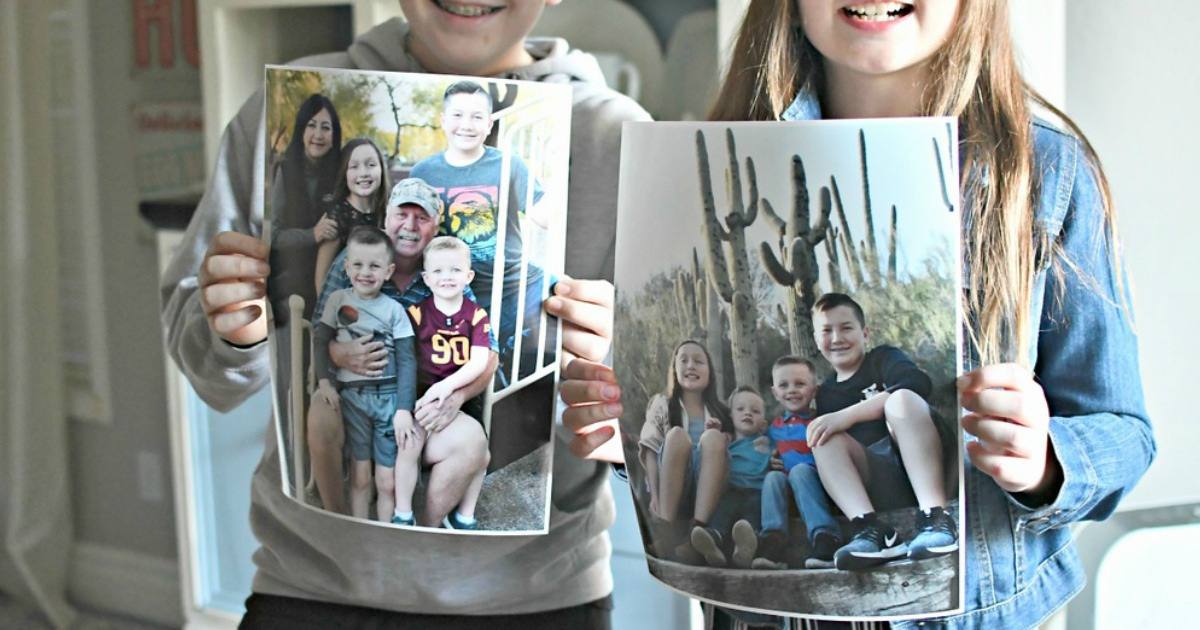 boy and girl holding up photo posters that show family pictures taken in the desert
