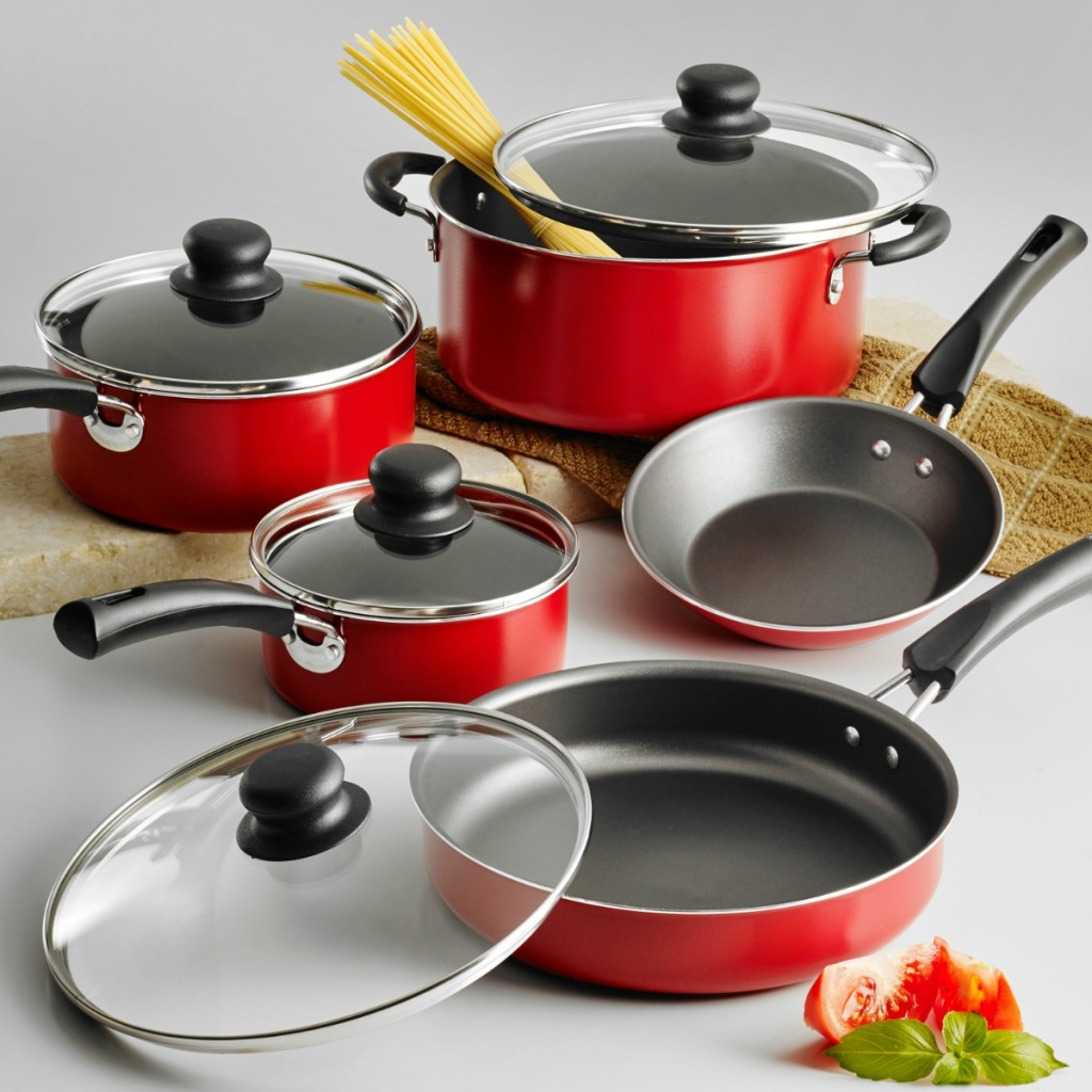 Large set of matching pots and pans on counter surface with towel