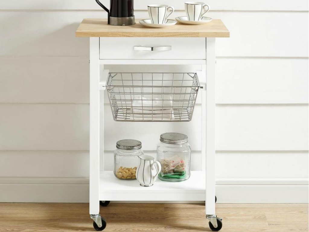 Small white kitchen cart with wooden counter top and wire basket