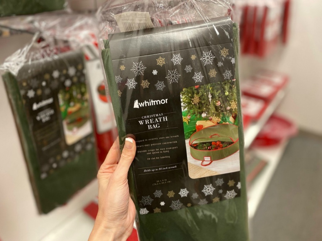 Green wreath storage bag in package in hand, in store