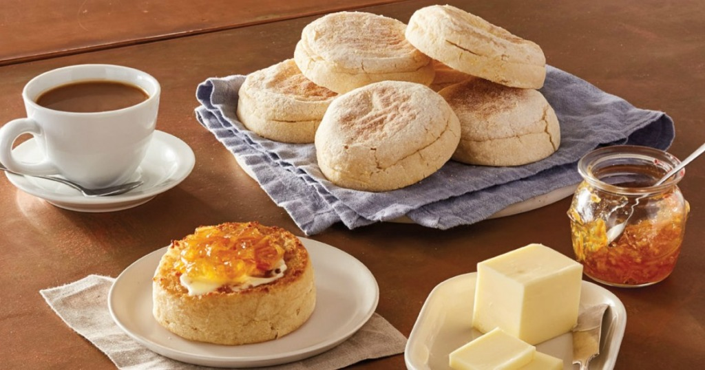 English muffins on a table with butter, cup of coffee and jam