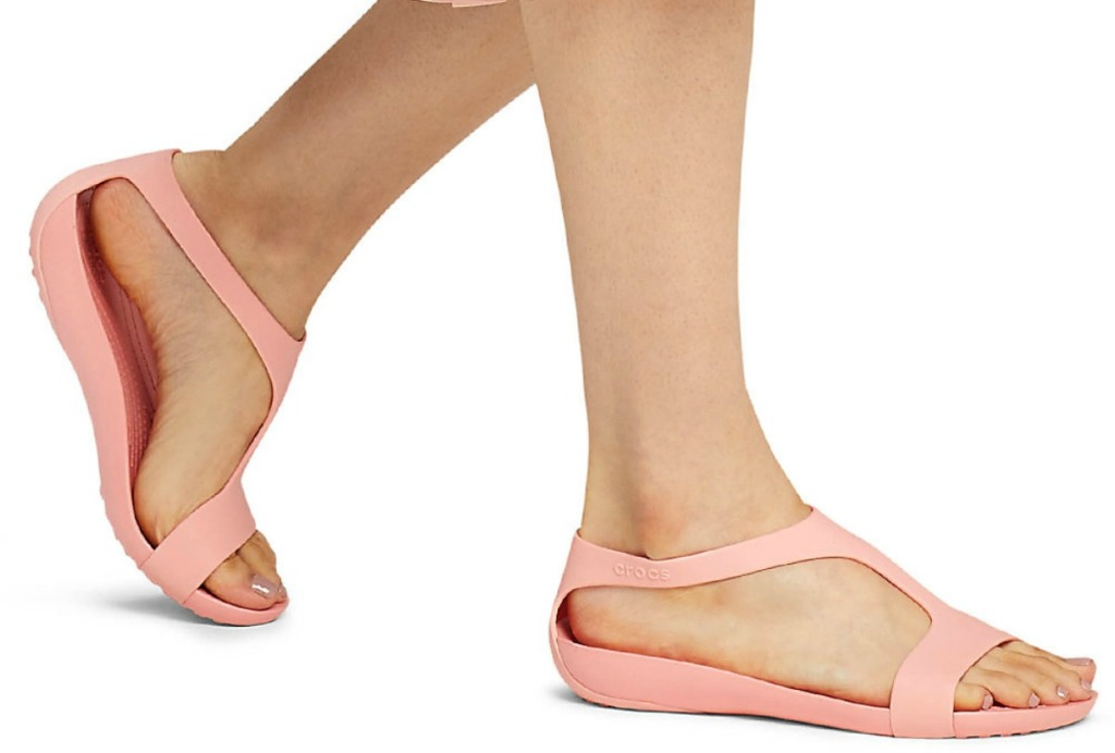 Woman wearing pink Crocs sandals