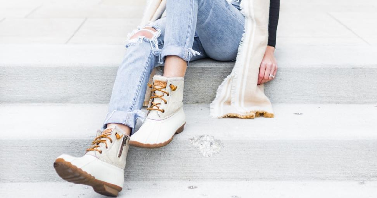 the legs of a lady sitting on cement steps, wearing ripped jeans and White Sperry boots