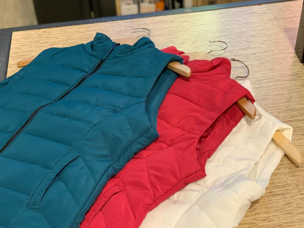 Women's puffer vests on hangers on table top