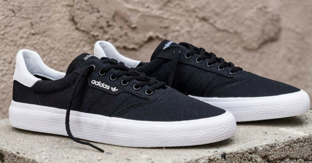 men's black and white adidas sneakers on a rock