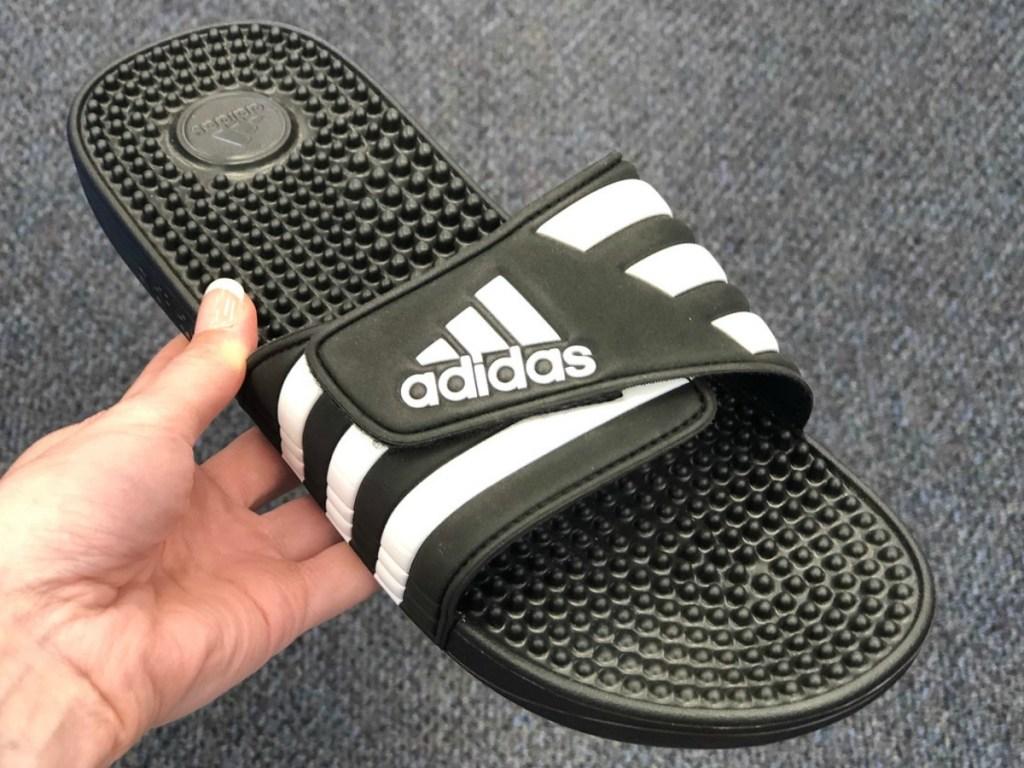 Single of men's slip on sandal in black with white adidas logo in hand near carpeted floor