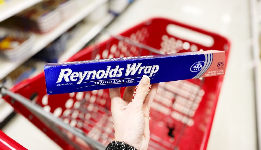 hand holding reynolds wrap aluminum foil with target cart in the background