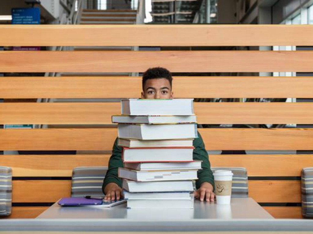 college student with stack of text books at table