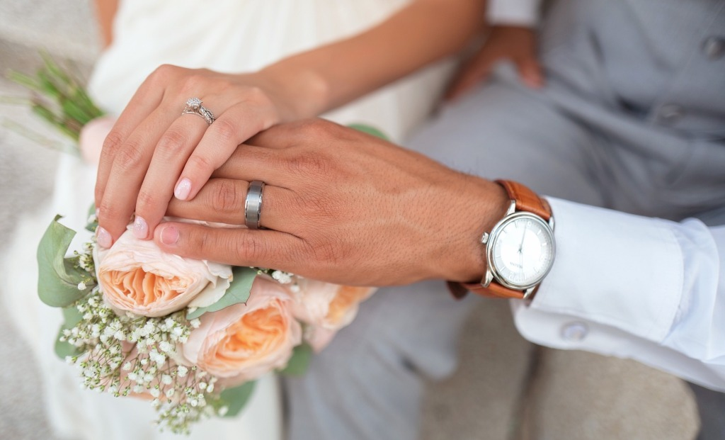 bride and groom hands with flowers