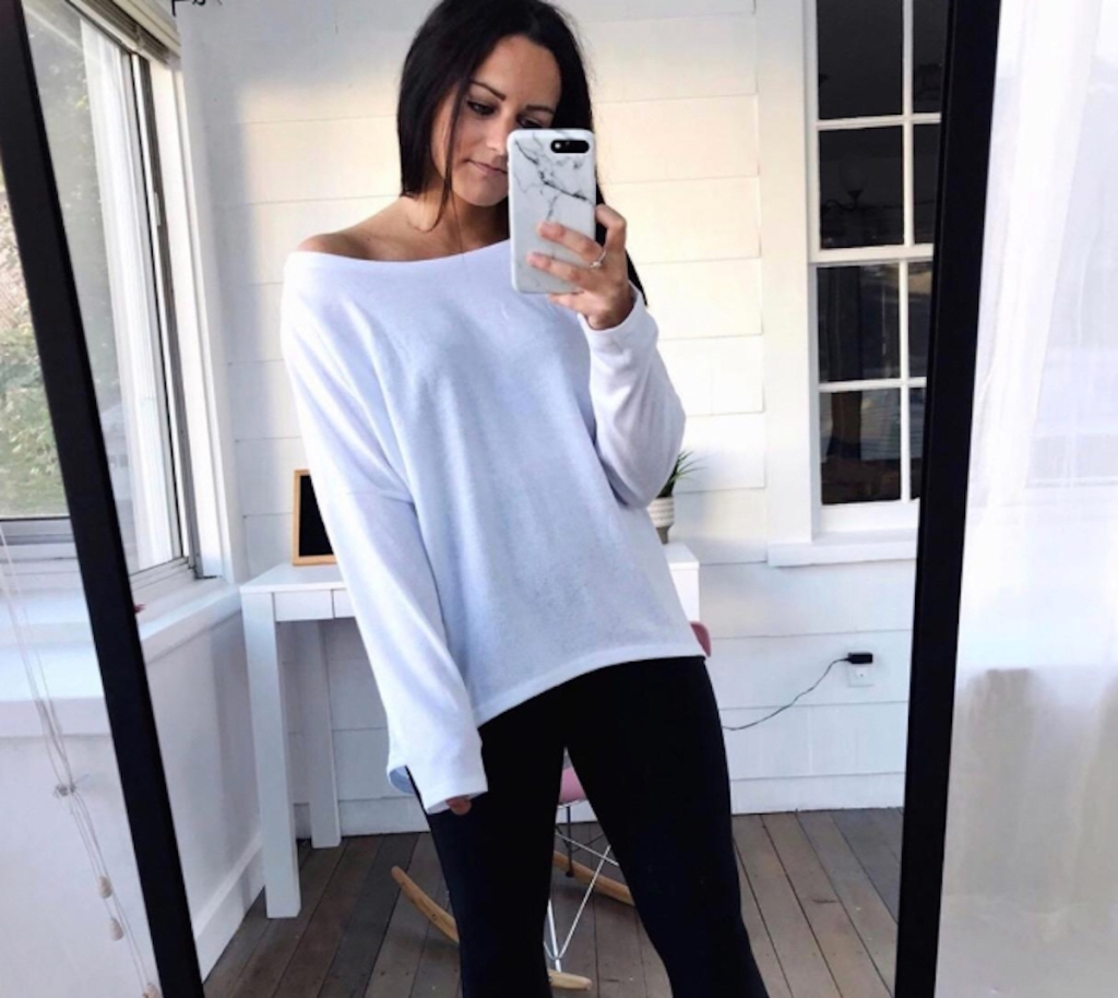 woman wearing white sweater and black leggings looking in the mirror