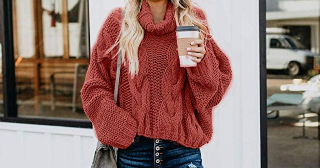 woman wearing rust red colored chunky knit sweater holding a coffee