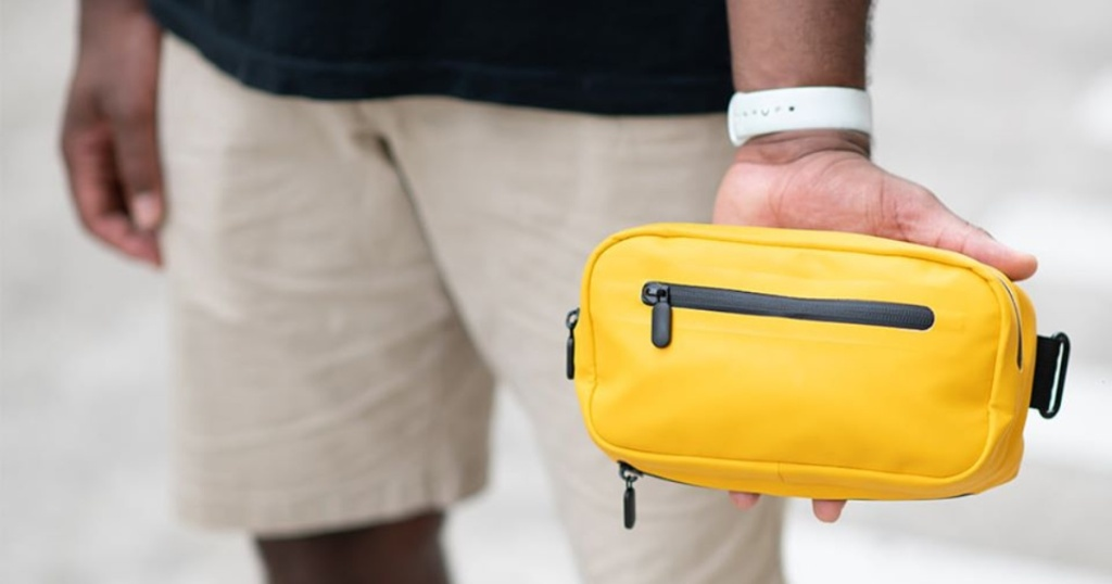 Man holding yellow fanny pack